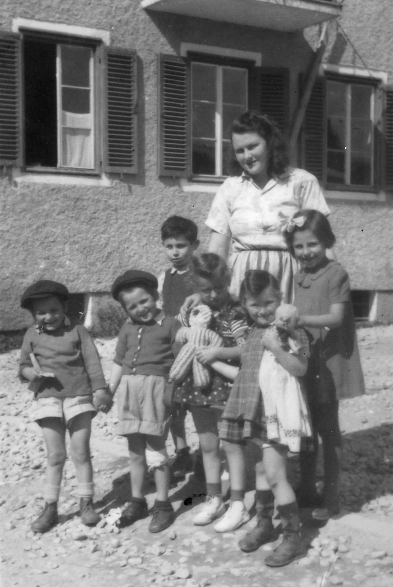 Young children, some holding dolls, pose with their teacher outside a building in a religious kibbutz in Salzburg Austria.  The teacher is Scheindel Trebitz.