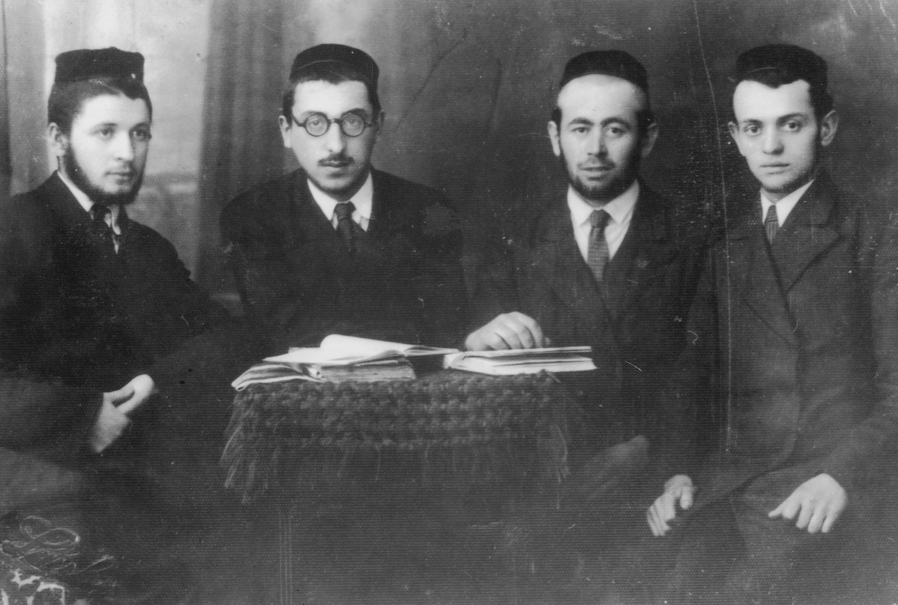Studio portrait of four students from the Tarnopol Yeshiva with religious texts.  Pictured on the far right is Yitzchok Scharf.