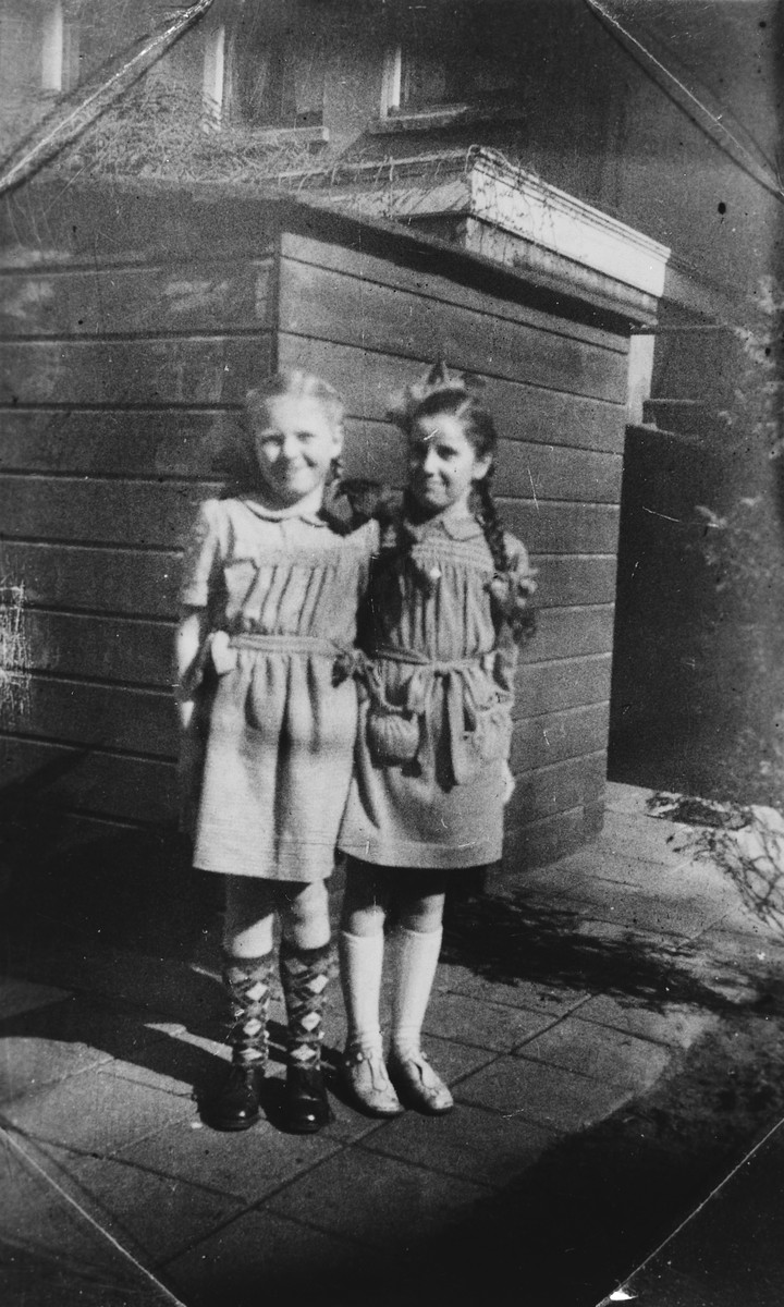Close-up portrait of two young girls, one of whom is a Jewish child in hiding.  Pictured is Rita Serphos.