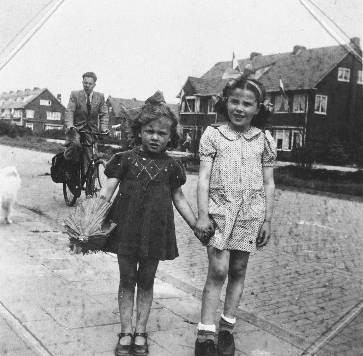 Two young girls, one of whom is a Jewish child in hiding, pose on a street of an unidentified Dutch town in front of a man on a bicycle.  Pictured is Rita Serphos.