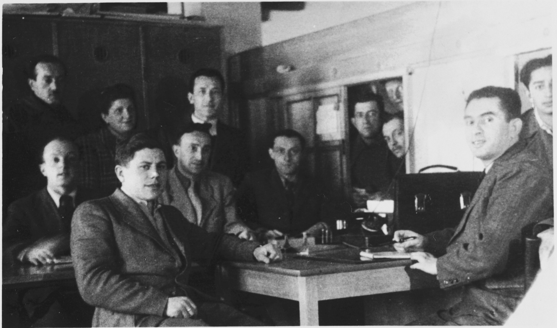 A group of men pose inside an administrative office in the Foehrenwald displaced persons' camp.  Pictured in the bottom left is Sam Spiegel, originally from Kozienice.  Also pictured is Fishl Burakowski, seated behind the desk in the center of the photo.
