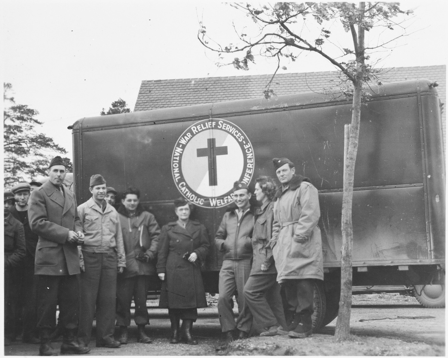 UNRRA workers stand next to an ambulance supplied by the National Catholic Welfare Conference (probably in the Foehrenwald displaced persons' camp).  Marion van Binsbergen Pritchard is pictured second from the right.