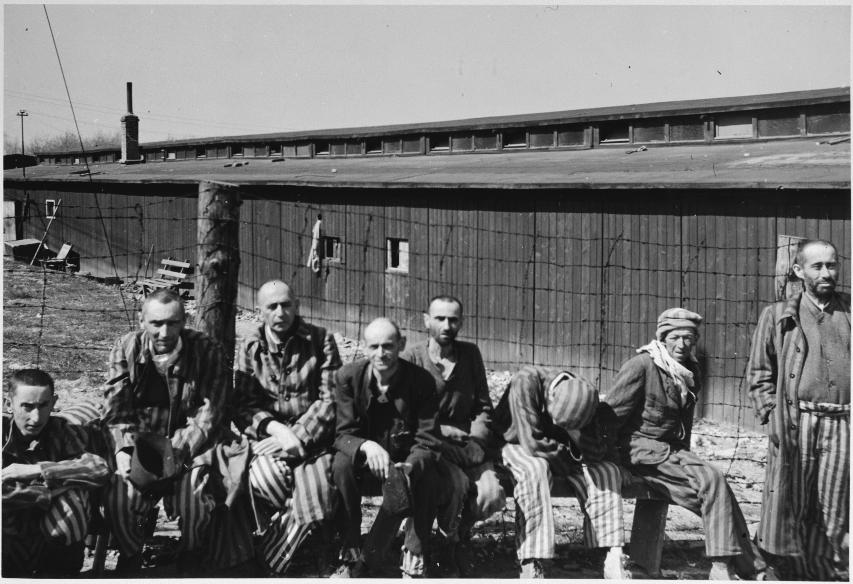 "Several Russian political prisoners sit by a fence after the liberation of Buchenwald.  The original caption reads, ""A typical group of Russian political prisoners.  Seldom is there a smile as they all lack interest in life."""