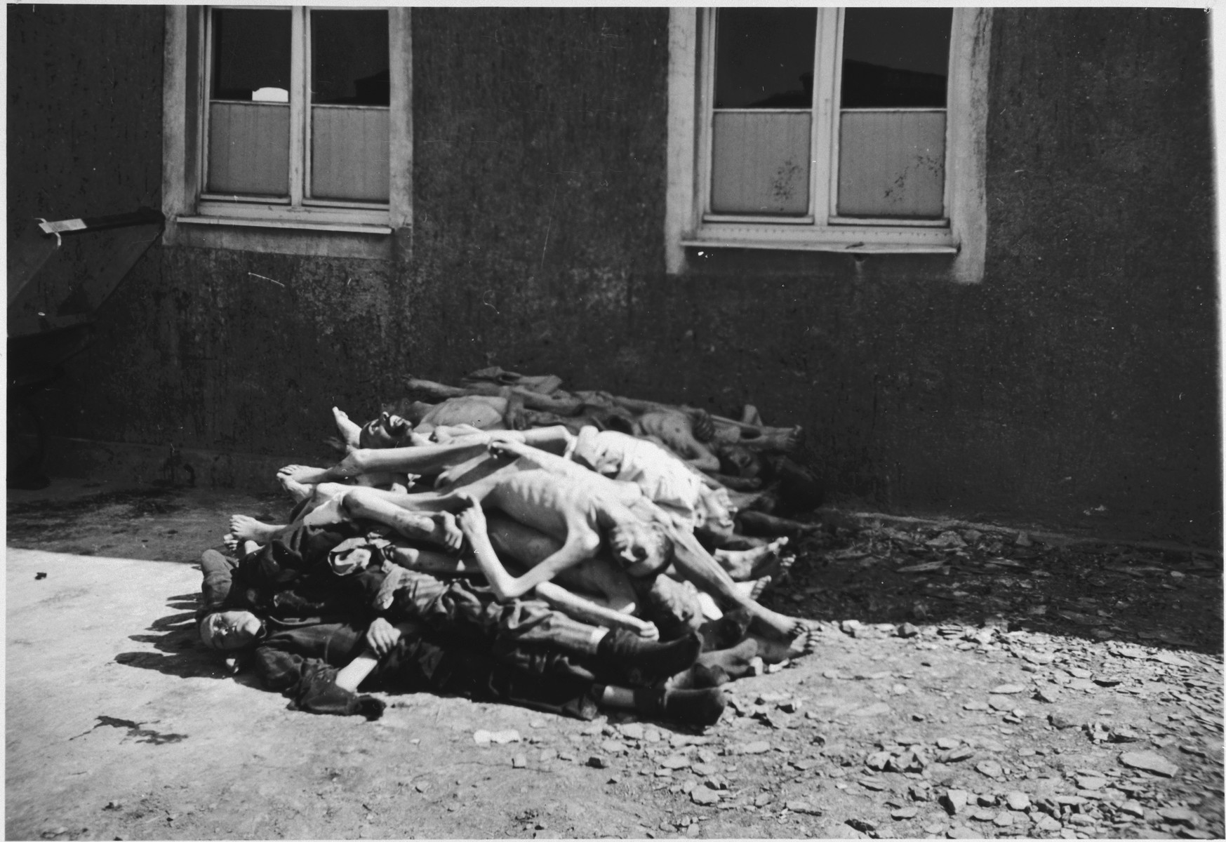 """A pile of corpses waits to buried at Buchenwald after the liberation.  The original caption reads, """"The last body on the top of this heap was thrown on just before the taking of this picture.  Three bodies were brought to this yard while pictures were being taken."""""""