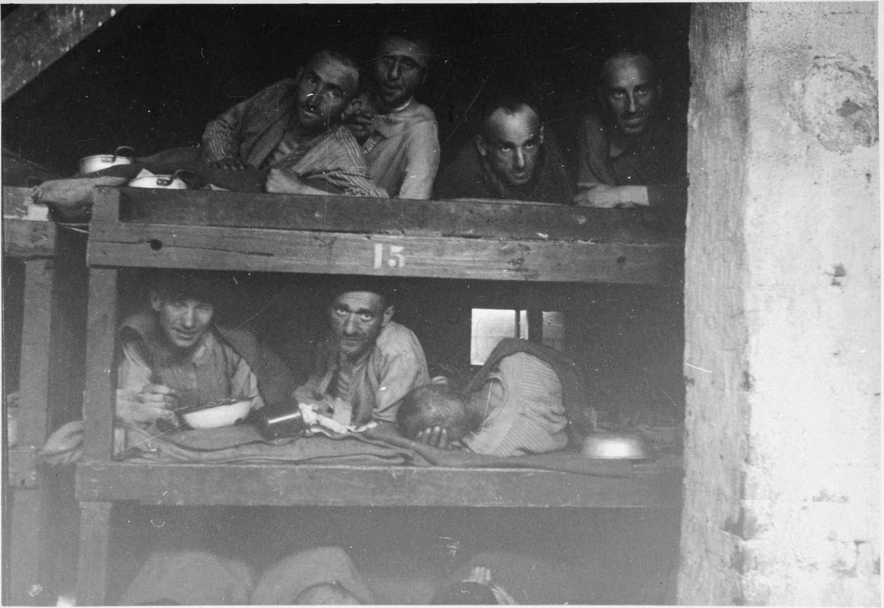 Several survivors stare as they lie down in the hospital bunks.