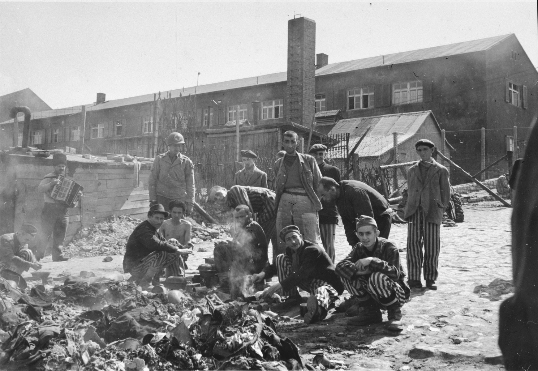 "Survivors of Buchenwald scrounge for food after liberation.  The original caption reads, ""A group of prisoners preparing extra nourishment.  They are given black bread and horse meat hash from the central mess."""