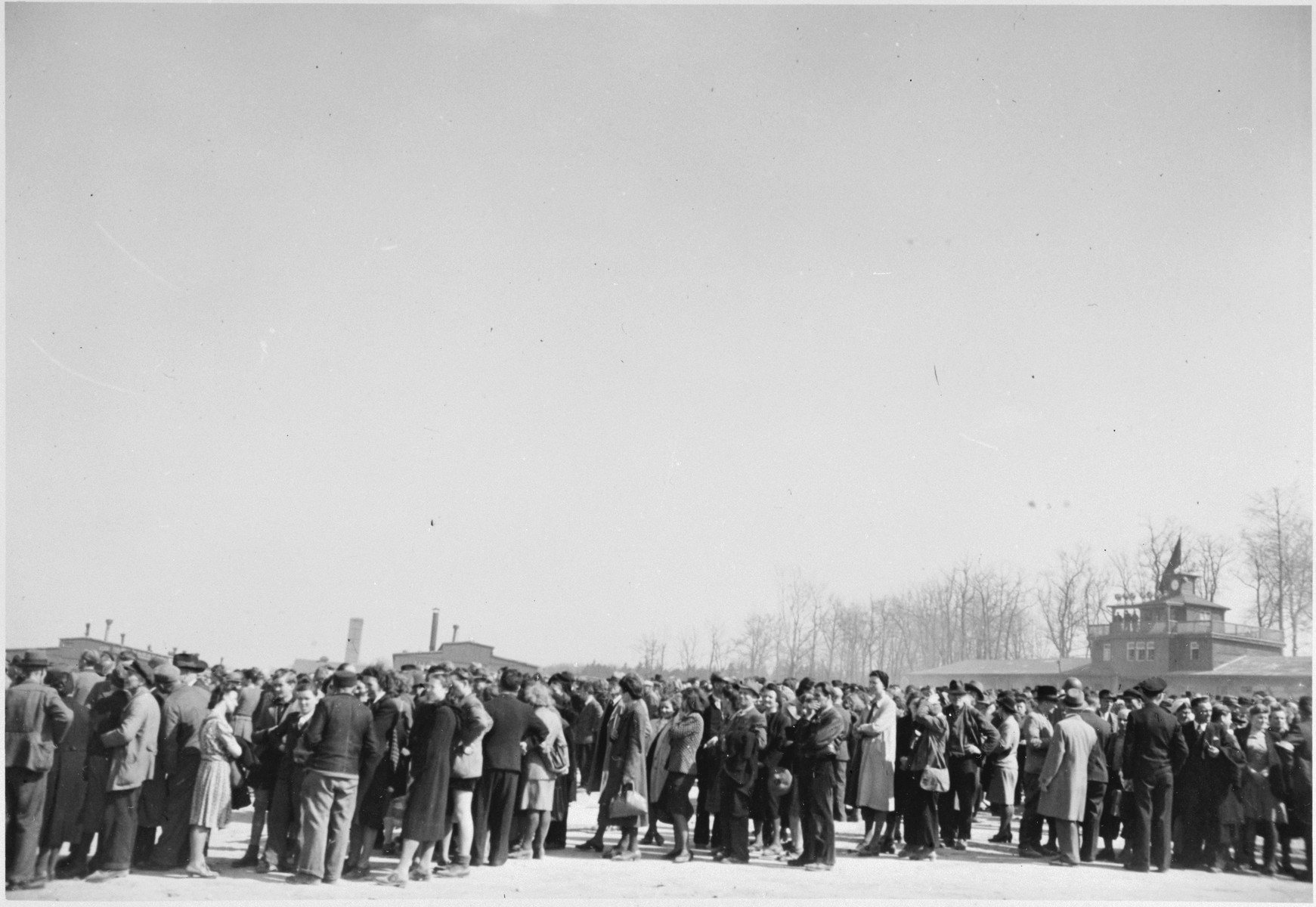 "German civilians are forced to wait in-line to tour the Buchenwald concentration camp.  The original caption reads, ""General Patton requested that over 1200 residents of Weimar visit the camp [Buchenwald] and see the horrors which had been wrought upon the political prisoners by the Gestapo""."