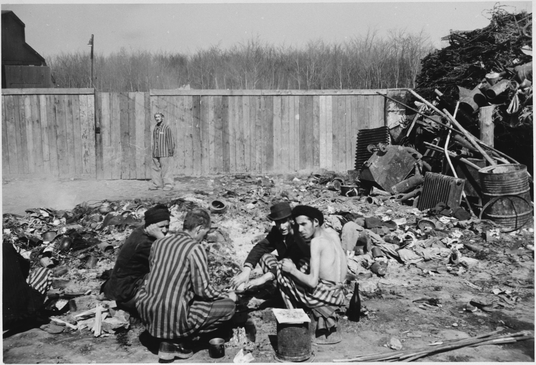 Survivors cook on scrap heaps to try to obtain some nourishment three days after liberation.