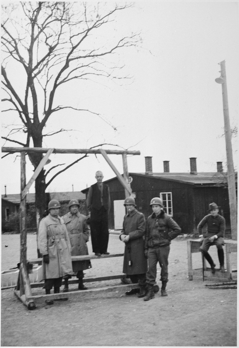 "A survivor reenacts how the hangings took place at Ohrdurf concentration camp, a sub-camp of Buchenwald.  The caption for the photo reads, ""The scaffold for public execution. The prisoner was hung from a chain noose. The plank was then pushed from under his feet. If he didn't die quickly he was hit over the head with a potato masher."""