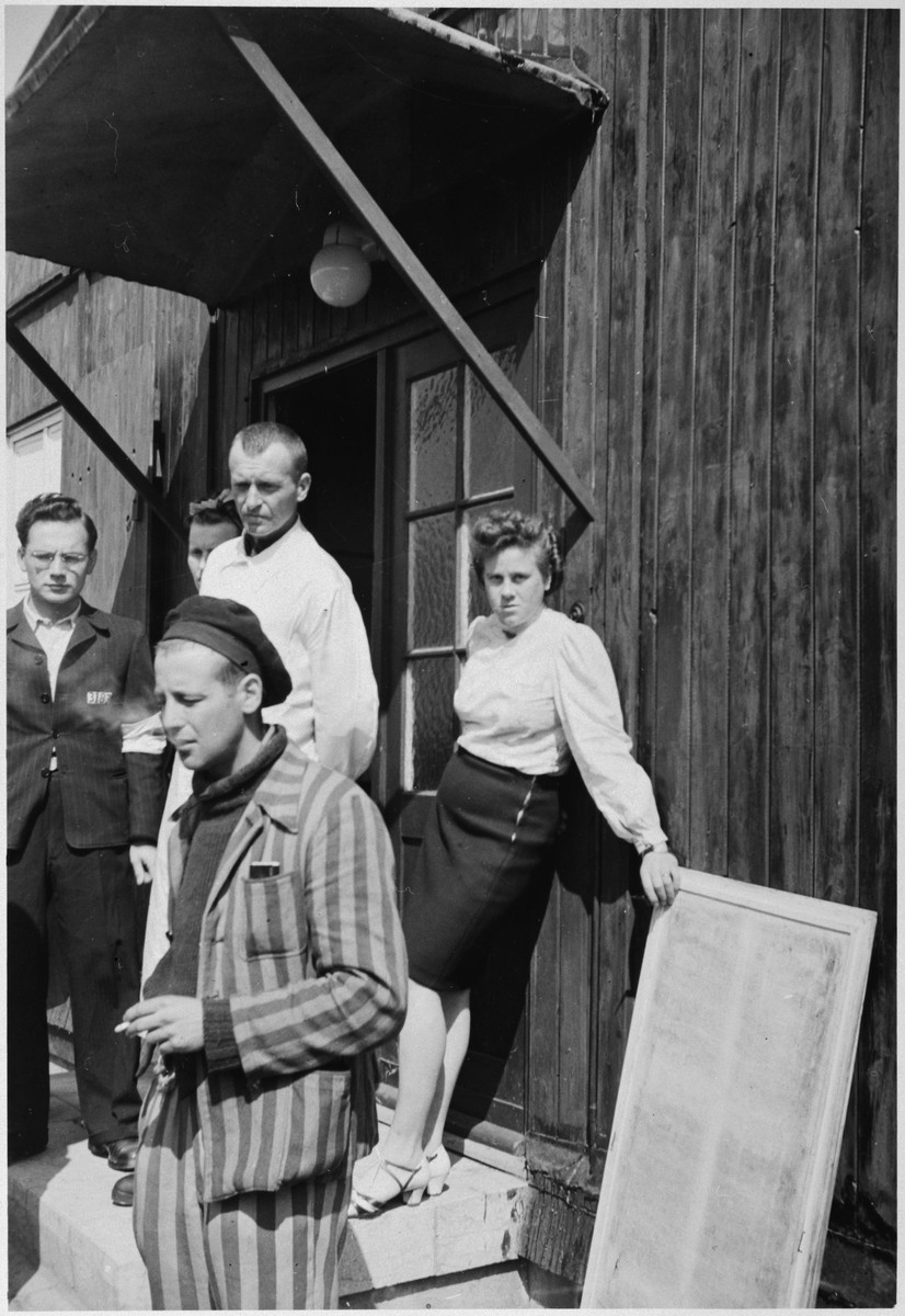 Survivors of Buchenwald, one of whom is smoking a cigarette, stand in front of a barrack.