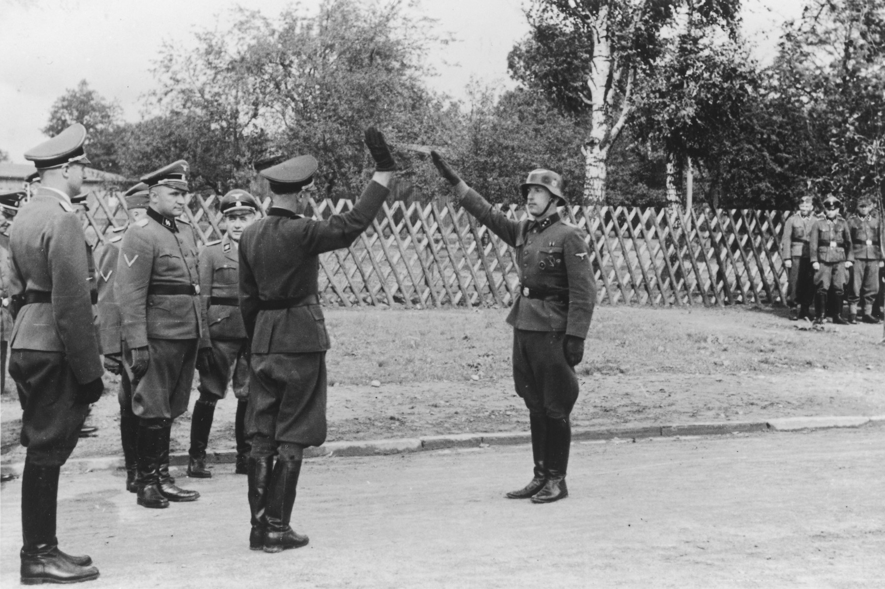 "A Nazi soldier salutes an officer, while several other officers stand in the background during the dedication of a new SS hospital in Auschwitz.  The official caption reads ""Einweihung des SS-Lazarettes in Auschwitz"" (Dedication of the SS Hospital in Auschwitz).  Pictured on the leftt are Dr. Eduard Wirths, Commandant Richard Baer and Karl Bischoff."