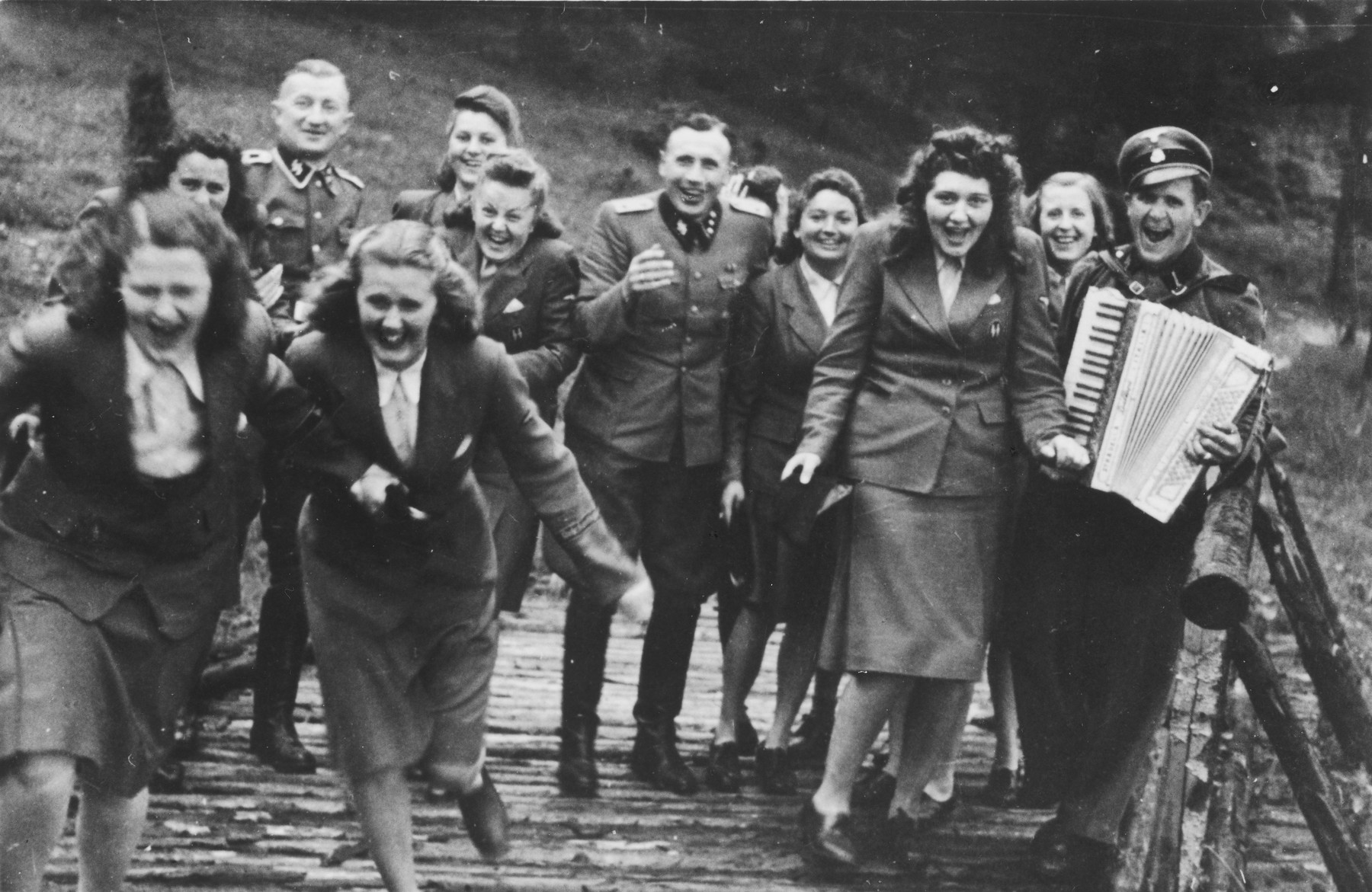 "Nazi officers and female auxiliaries (Helferinnen) run down a wooden bridge in Solahuette.  The man on the right carries an accordion.  Karl Hoecker is pictured in the center.  The original caption ""Regen aus heiteren Himmel"" [Suddenly, it started to rain.]"