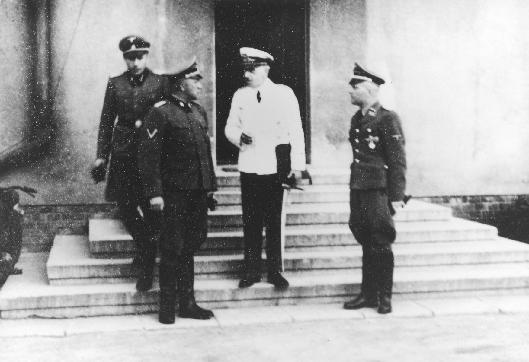 "Air Force General Quade visits Auschwitz to deliver a lecture entitled ""Germany's Aerial Warfare Leadership"".  Also pictured are SS officers Richard Baer, Karl Hoecker and Rudolf Hoess.  Picture taken at the Fuehrerheim in Auschwitz."