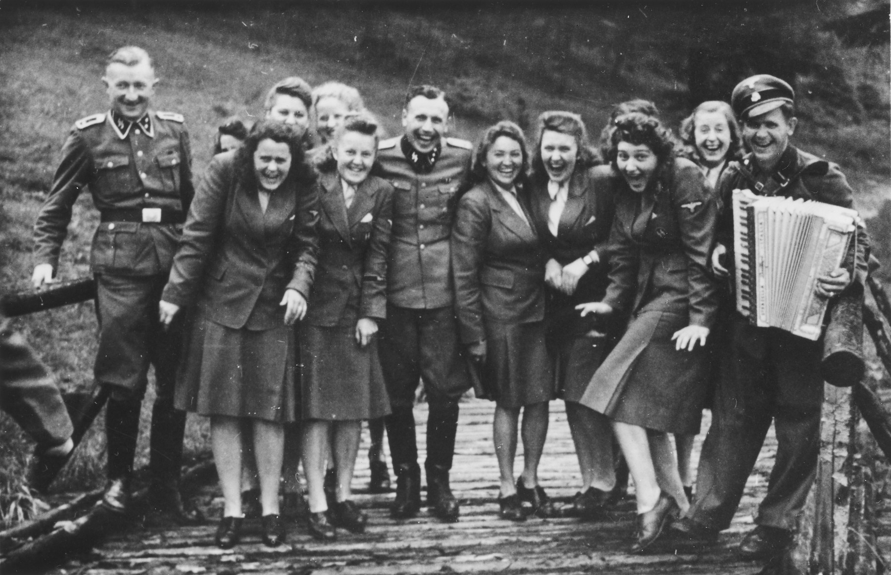 "Nazi officers and female auxiliaries (Helferinnen) pose on a wooden bridge in Solahuette. The man on the right carries an accordion.   Karl Hoecker is pictured in the center.  The original caption ""Regen aus heiteren Himmel"" [Suddenly, it started to rain.]"