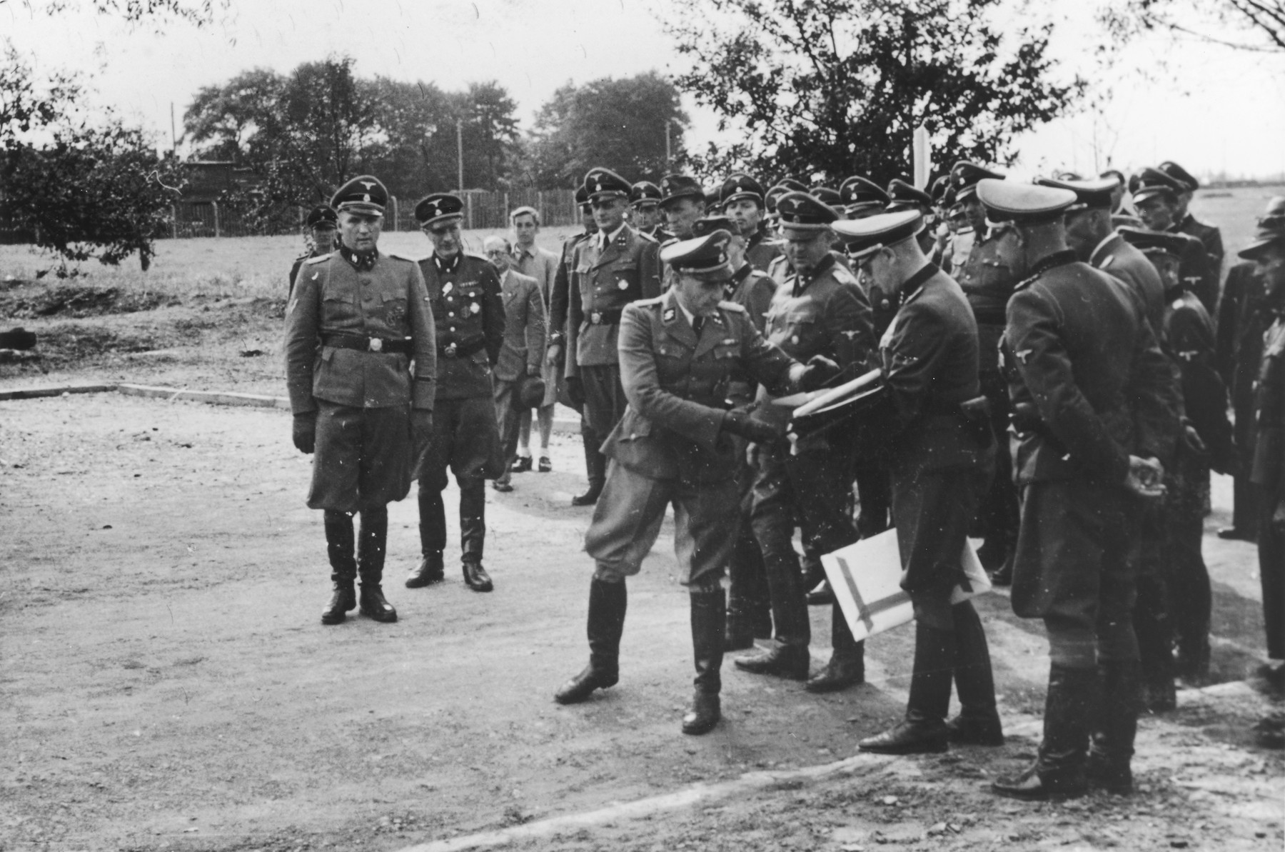 "Nazi officers watch the presentation of a document during the dedication of the new SS hospital in Auschwitz.  The original caption reads ""Die Ubergabe"" (the handover).  The ceremony marks the transfer of documents and authority from the construction department to the camp upon completion of the project.  Commandant Richard Baer stands on the far left. Karl Bischoff, head of construction in Silesia, is receiving the official documents from (most probably Werner Jothann) in preparation for handing them to Baer.  Karl Moeckel is looking down at the exchange of documents.  Also pictured are Drs. Enno Lolling, Eduard Wirths and Carl Clauberg.  Heinz Baumkoetter is in the back looking up slightly."