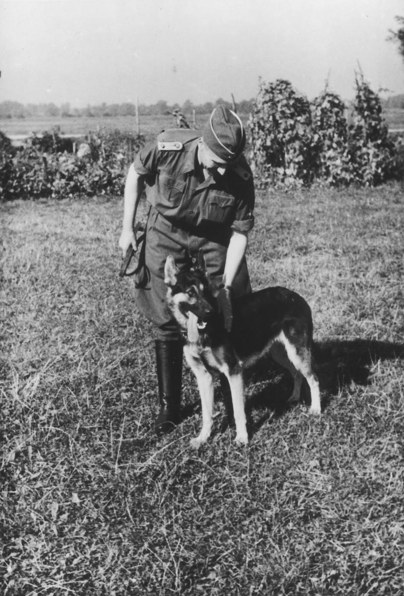 "SS officer Karl Hoecker pets his dog.  The original caption reads ""Mein Schaeferhund ,Favorit'"" [My Shephard dog ,Favorit']."