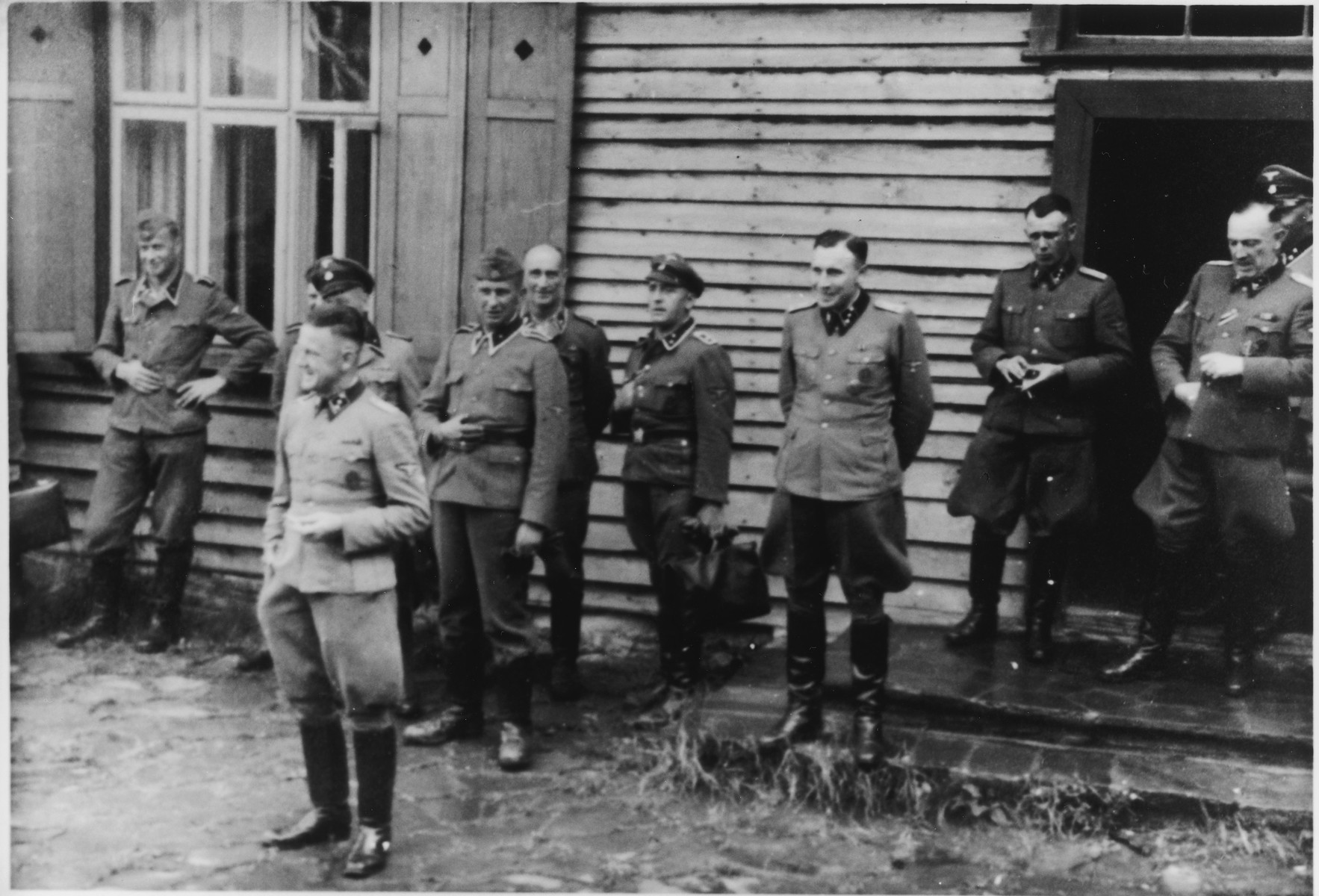 Group portrait of Nazi officers standing in front of a building in Solahutte, the SS retreat outside of Auschwitz.  Among those pictured are Franz Hoessler (front) and Karl Hoecker (third from the right).  Also pictured on the far right is SS-Obersturmführer Max Sell (served from 1943 to1945 first Arbeitseinsatzführer in Auschwitz and afterwards in Mittelbau-Dora.)  Also pictured in the back center is  scha. Hermann Baltasar Buch (30.12.1896-10.07.1959).  From 1943 until September 1944 Buch was in charge of the crematory IV in Birkenau.  [Based on the officers visiting Solahutte, we surmise that the photographs were taken to honor Rudolf Hoess who completed his tenure as garrison senior on July 29.]