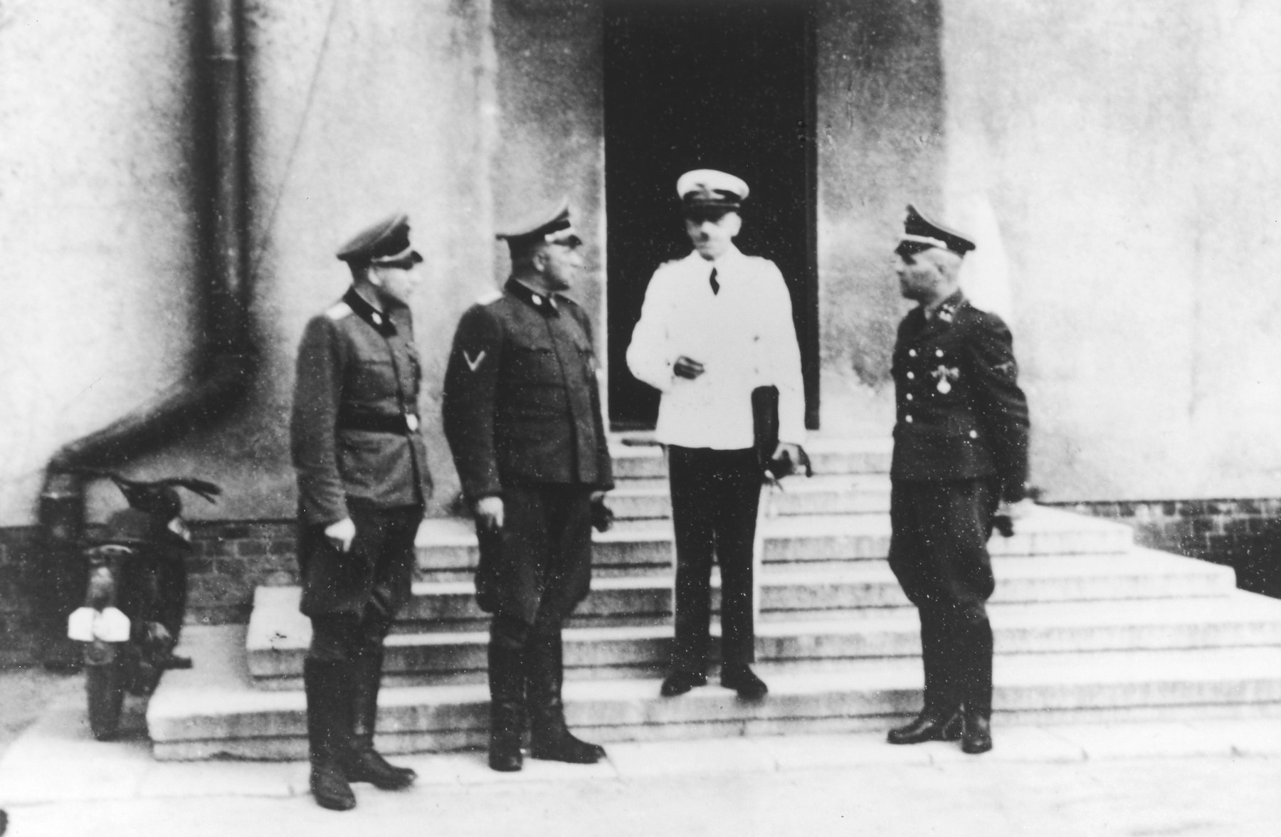 "Air Force General Erich Quade visits Auschwitz to deliver a lecture entitled ""Germany's Aerial Warfare Leadership"".  Also pictured are SS officers Richard Baer, Karl Hoecker and Rudolf Hoess.  Picture taken at the Fuehrerheim in Auschwitz."