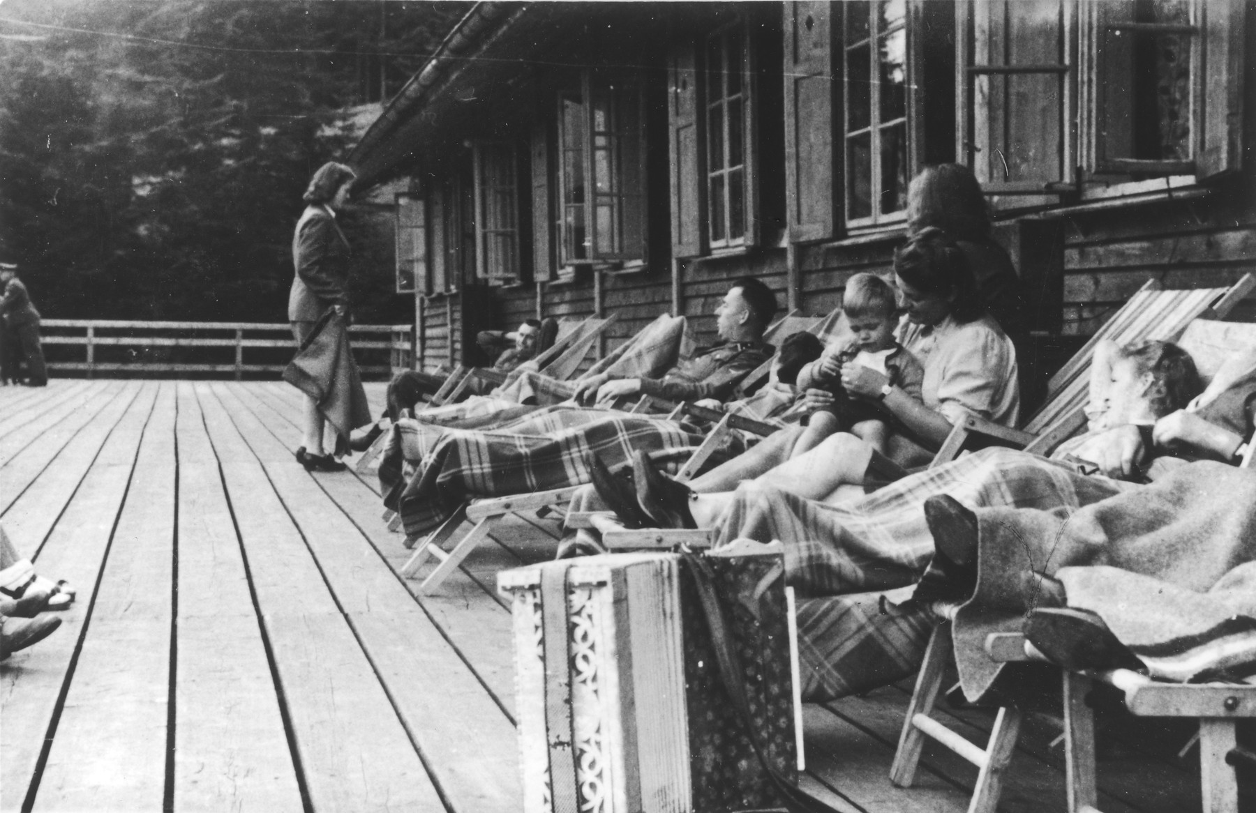 "SS officers together with women and a baby relax on lounge chairs on a deck in Solahuette.     The original caption reads ""On the terrace of the lodge""."