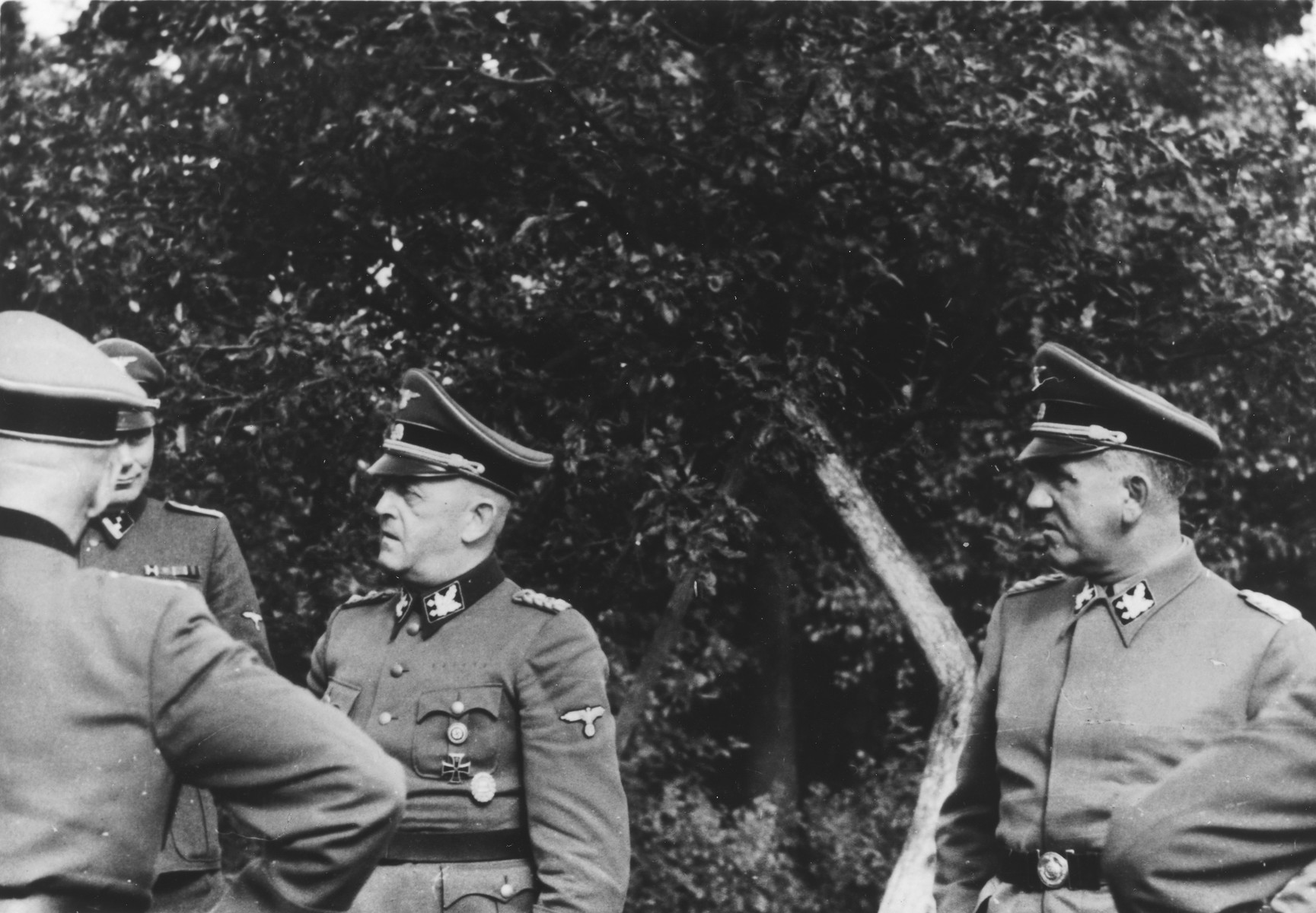 """SS officers Oswald Pohl (left) and Ernst Schmauser (center) visit Auschwitz.  Josef Kramer is pictured on the far left partially obscured.  The original caption reads: """"SS Ogrupf. Pohl and Schmauser in Auschwitz, 1944."""""""