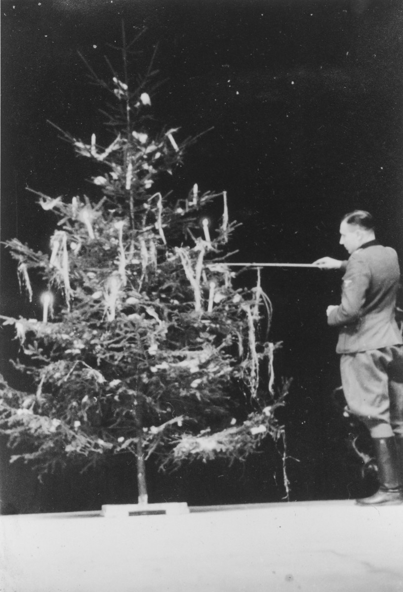 """SS officer Karl Hoecker lights a candle on a Christmas tree only weeks before the liberation of Auschwitz.   The original caption reads """"Julfeier 1944"""" (the Nazi name for a pre-Christian Yule celebration)."""