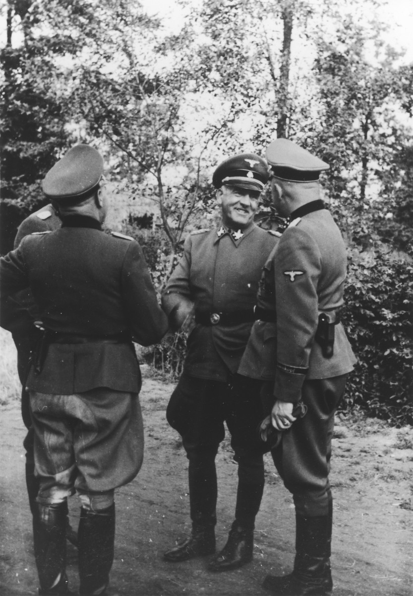 SS General Oswald Pohl pays an official visit to Auschwitz.  He is talking to Auschwitz Commandant Richard Baer who had previously served as Pohl's adjutant.