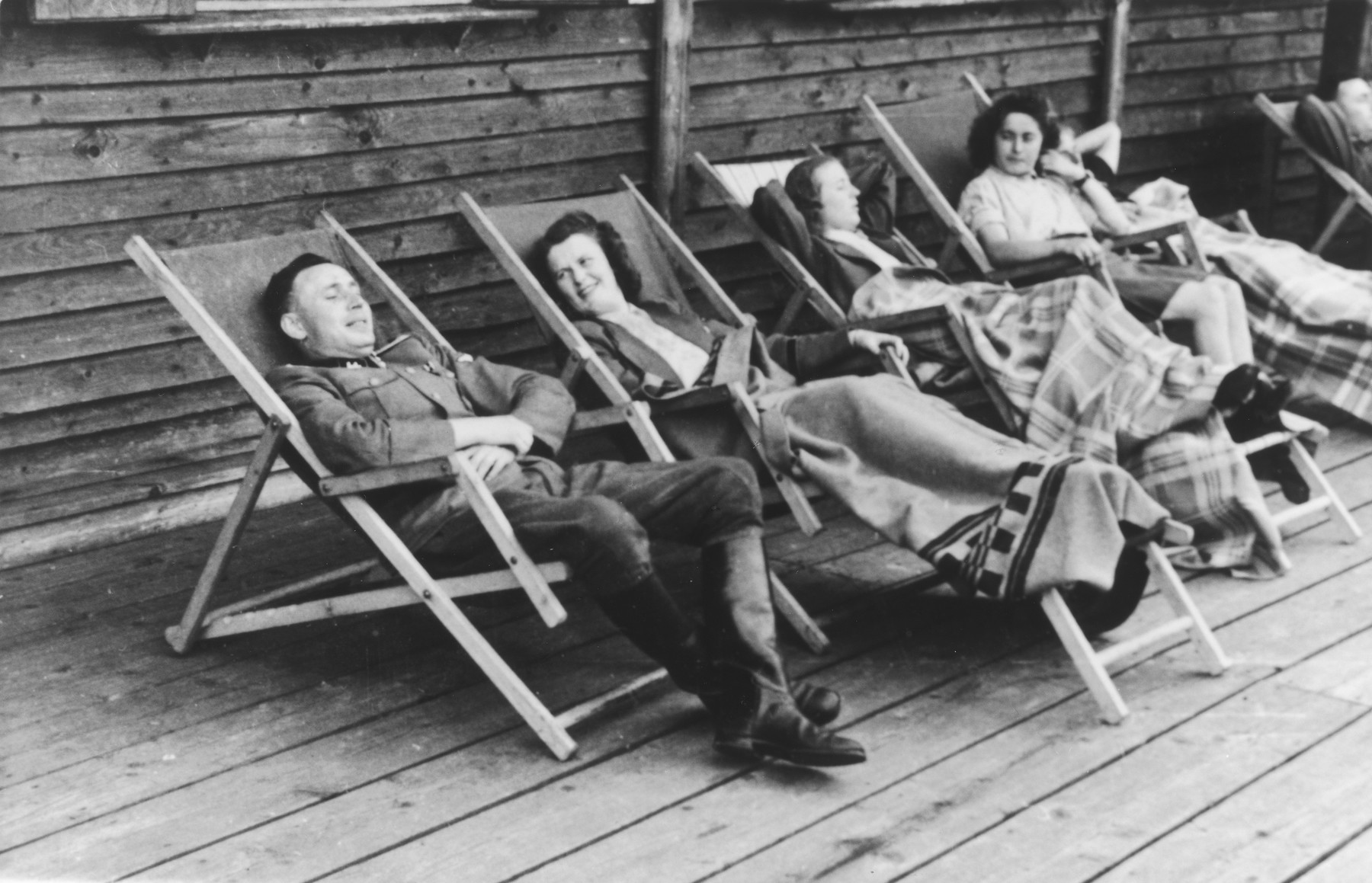 """SS officer Karl Hoecker relaxes with women in lounge chairs on the deck of the retreat in Solahuette.  The original caption reads """"On the terrace of the lodge""""."""