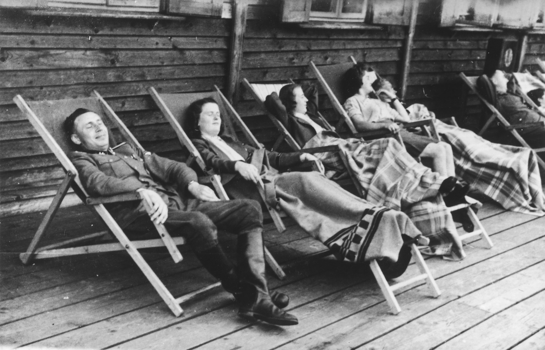 "SS officer Karl Hoecker and some women relax on lounge chairs on a deck in Solahuette.   The original caption reads ""On the terrace of the lodge."""