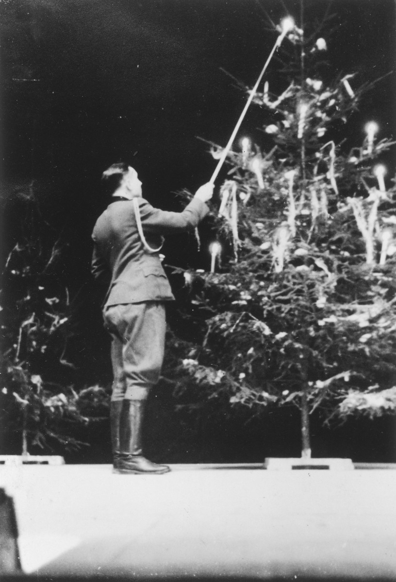 "SS officer Karl Hoecker lights a candle on a Christmas tree only weeks before the liberation of Auschwitz.   The original caption reads ""Julfeier 1944"" (the Nazi name for a pre-Christian Yule celebration)."