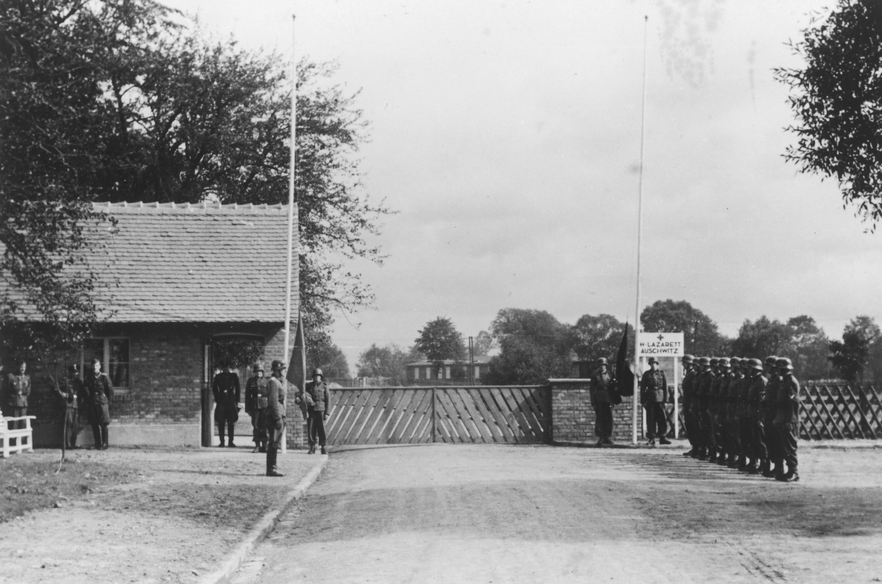 "Nazi troops stand at attention during the dedication of the new SS hospital in Auschwitz.    The official caption reads ""Einweihung des SS-Lazarettes in Auschwitz"" (Dedication of the SS Hospital in Auschwitz).  Pictured is the entrance to the SS hospital with gate, gate house and flag posts."