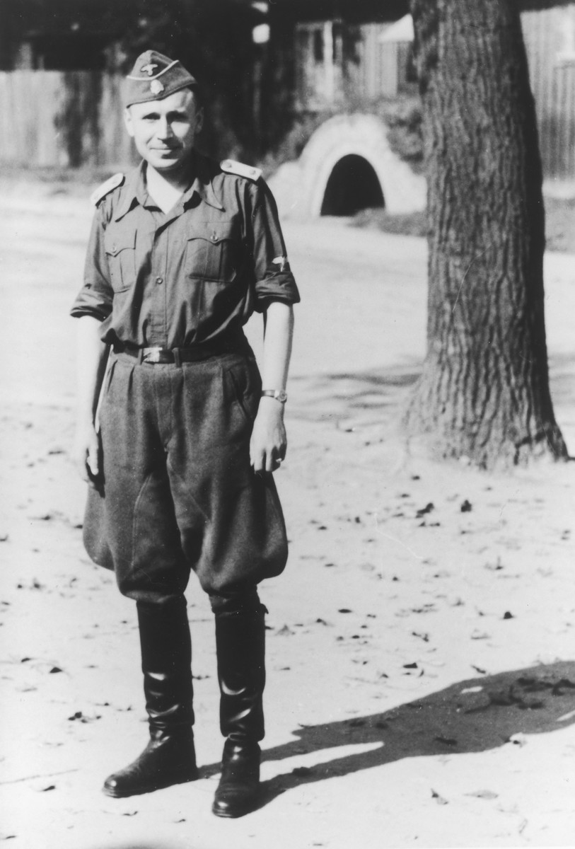 Portrait of SS officer Karl Hoecker with his sleeves rolled up standing in front of an air-raid shelter.