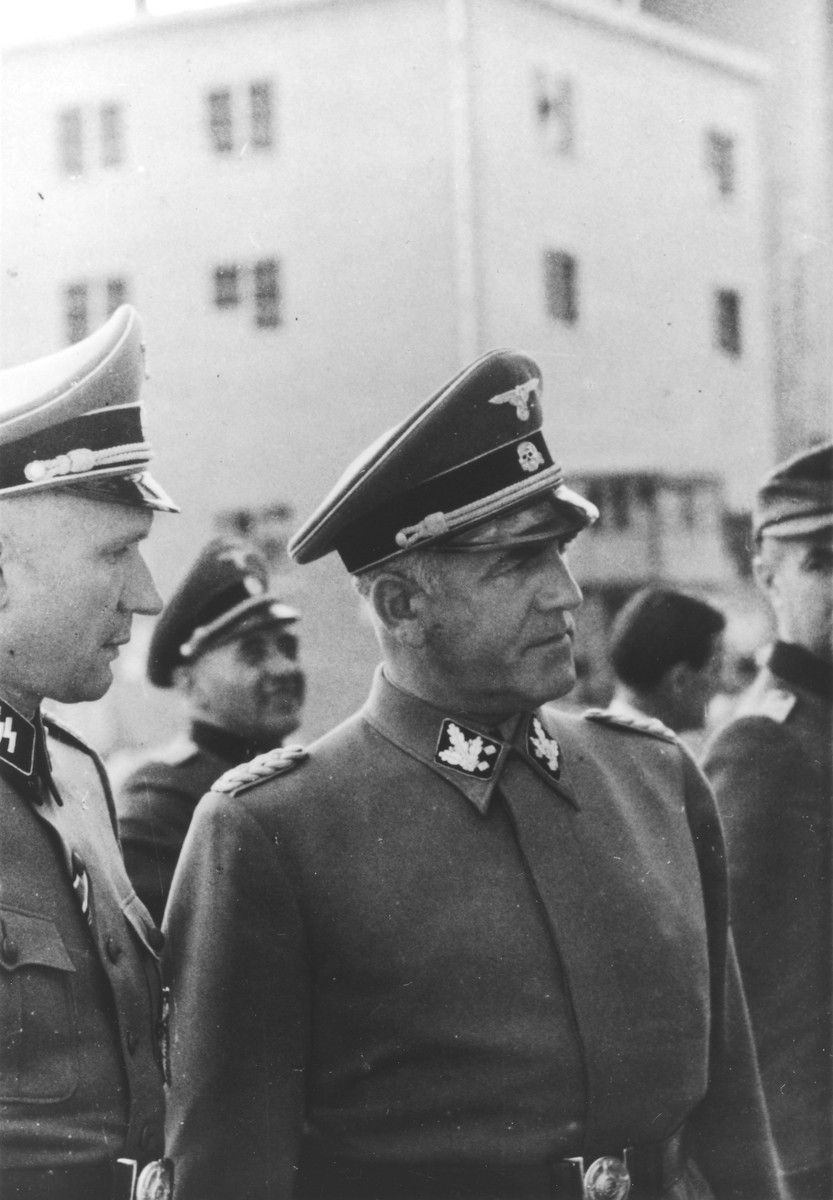 SS General Oswald Pohl pays an official visit to Auschwitz accompanied by Auschwitz Commandant Richard Baer who had previously served as his adjutant.  In the background between Baer and Pohl is Karl Bischoff.