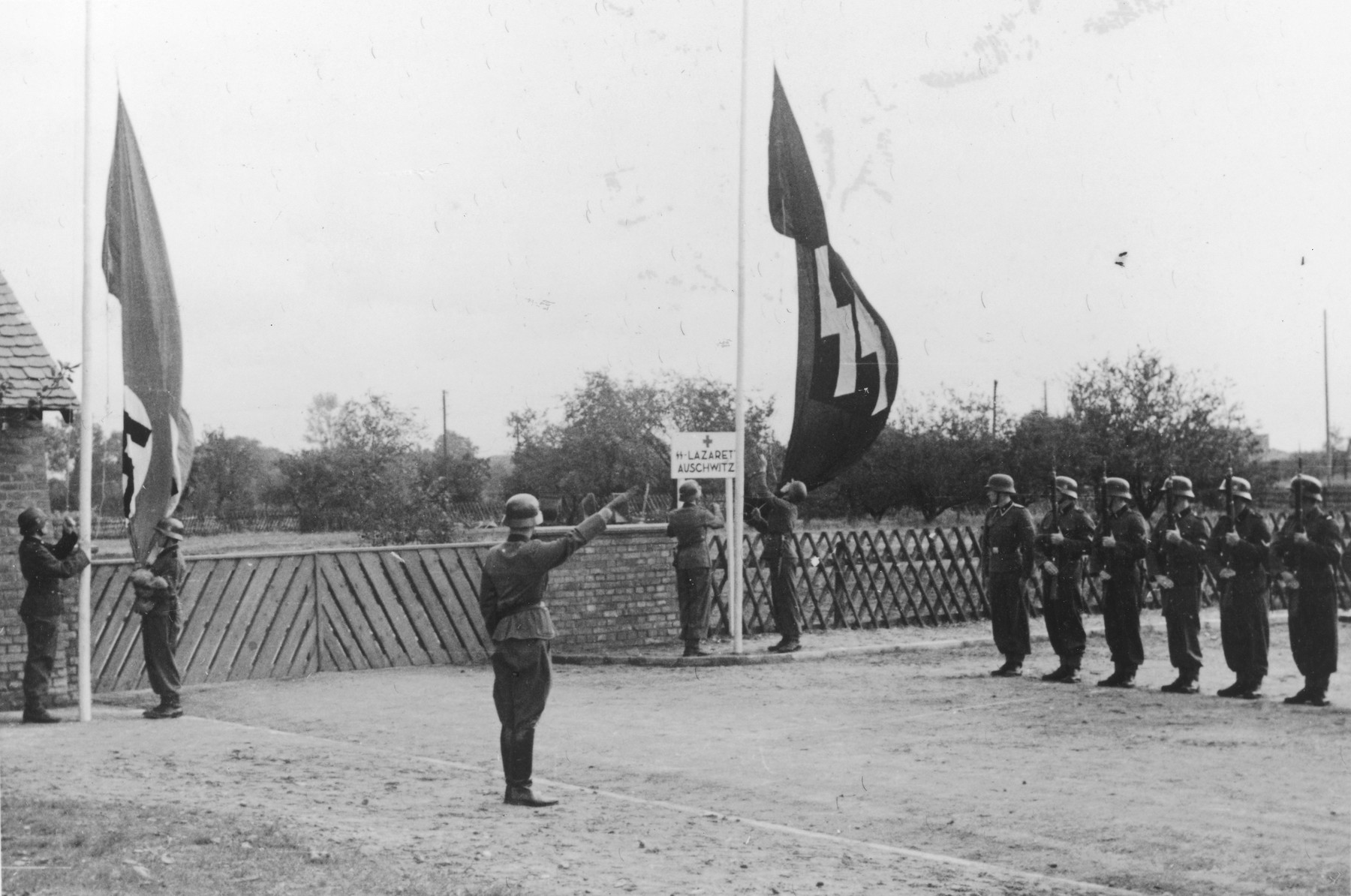 "A Nazi soldier salutes as the Nazi and SS flags are raised while a line of troops stand with rifles at attention during the dedication of a new SS hospital in Auschwitz.   The official caption reads ""Einweihung des SS-Lazarettes in Auschwitz"" (Dedication of the SS Hospital in Auschwitz)."