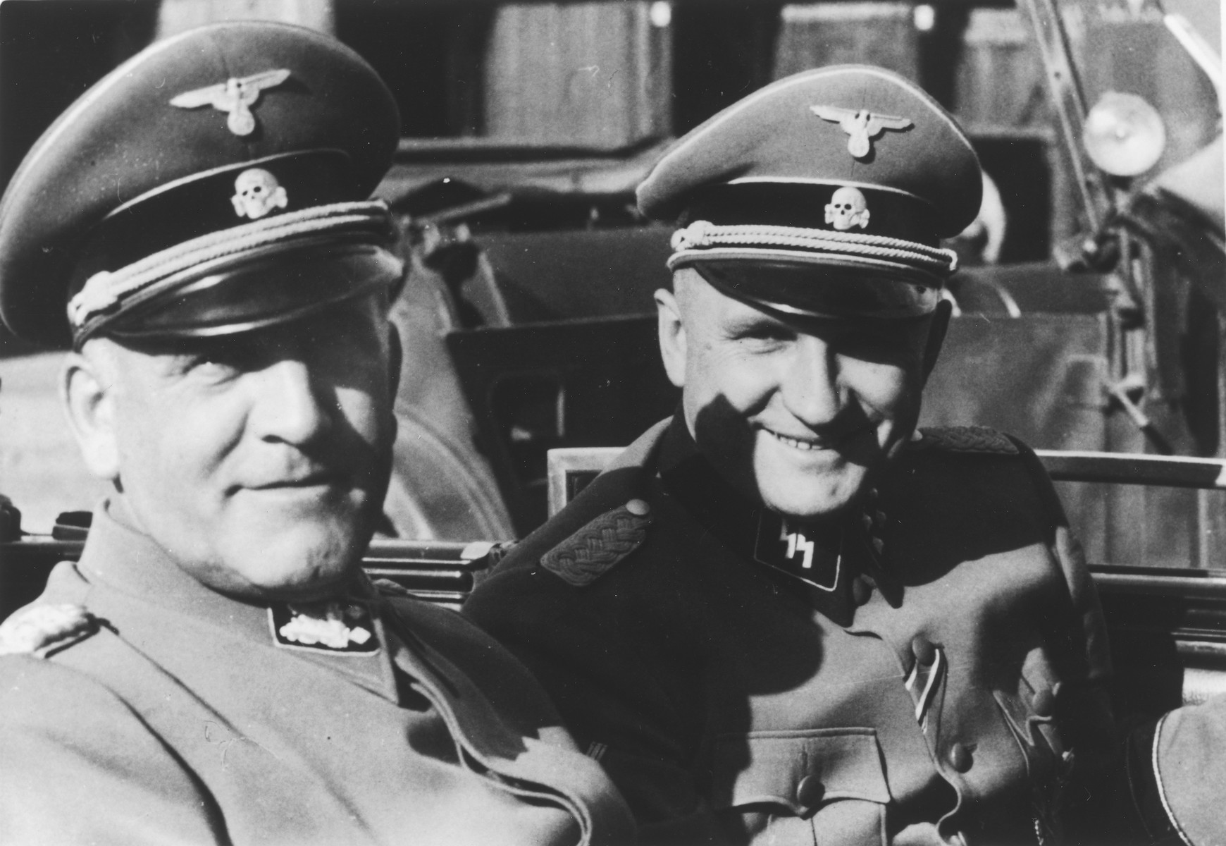 "Commandant Richard Baer (right) accompanies Oswald Pohl (left) during an official visit to Auschwitz by automobile.   Richard Baer had been Pohl's deputy before being assigned to Auschwitz.  The original caption reads: ""SS Ogrupf. Pohl and Schmauser in Auschwitz, 1944."""