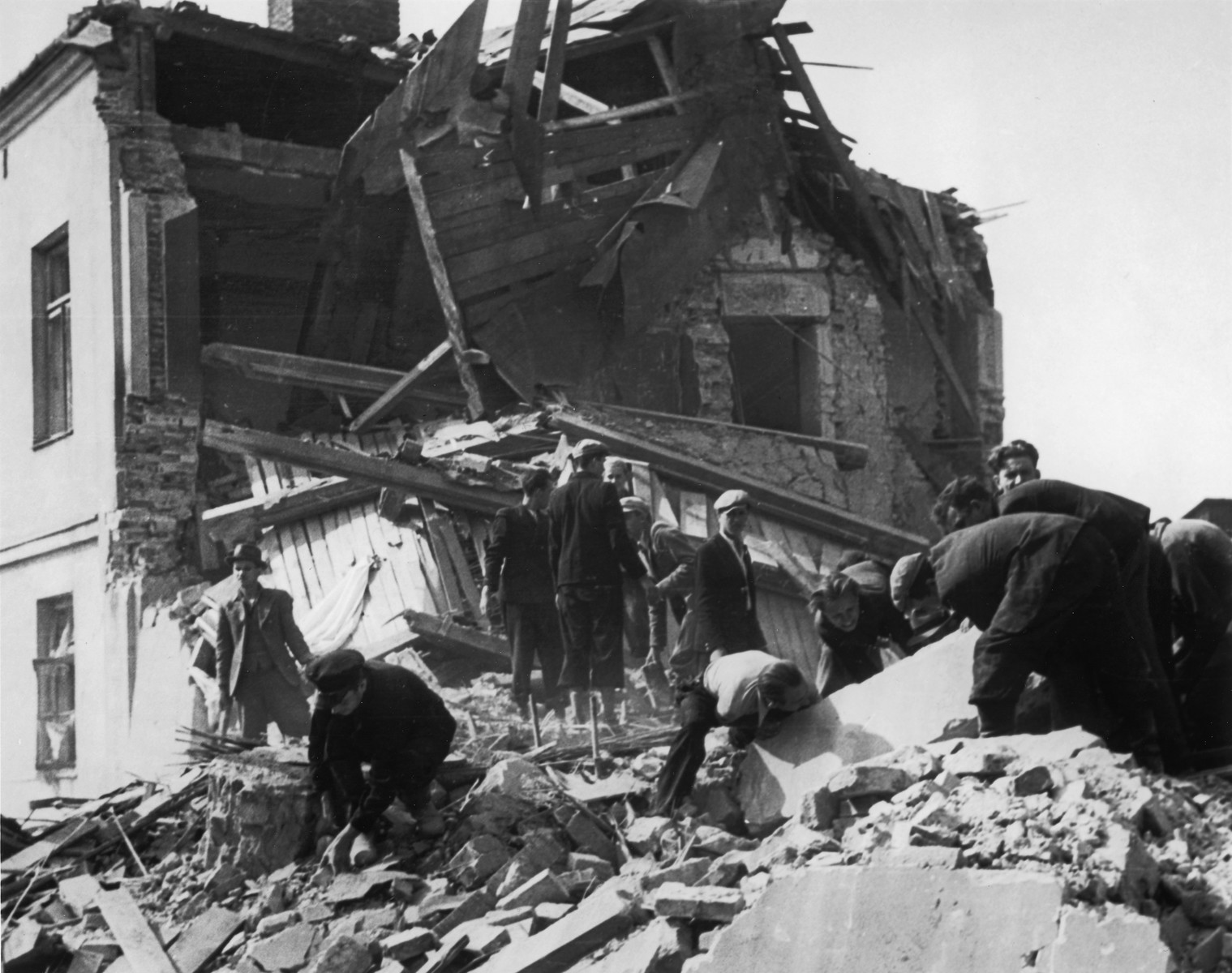 "Polish civilians remove bodies from the ruins of suburban Warsaw after a German air raid.  Original AP/Wide World caption reads:  ""First original picture made during Warsaw siege.  Fourteen persons were buried on Sept. 15 in collapse of this apartment in Novo Brodno, Warsaw suburb, when the German 'line' was less than a mile away.  Residents are shown attempting to dig out bodies shortly after the bomb fell.  This picture was made by Julien Bryan, American traveler and lecturer, following his arrival in Warsaw Sept. 7, after the Polish government,..photographers had left the..."""