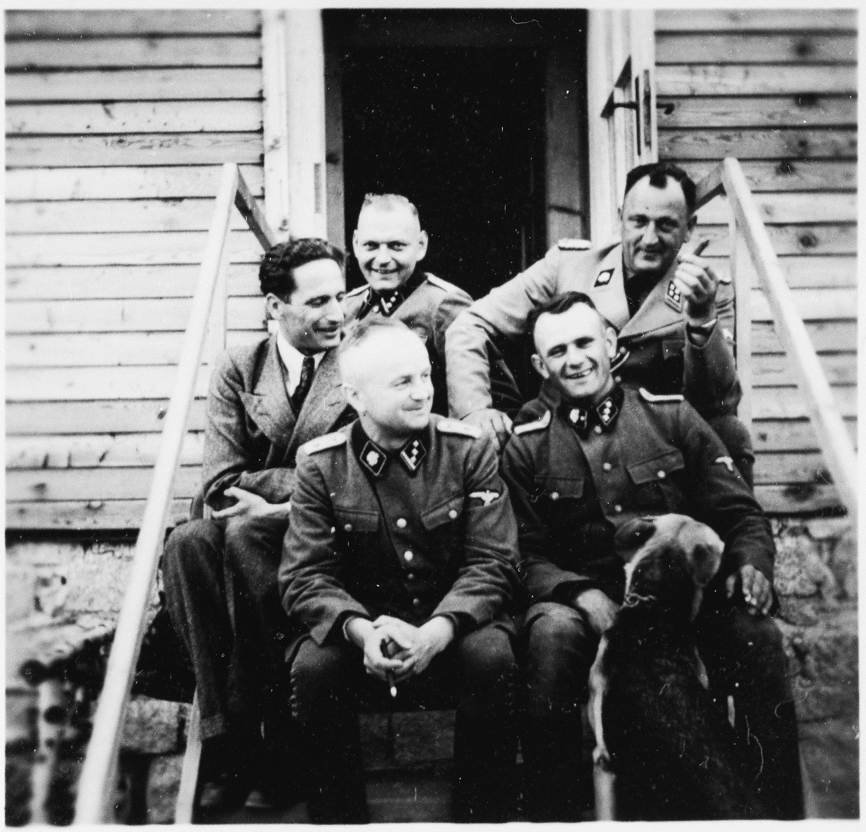 Five SS officers sit on the outside steps to a wooden building in Gross-Rosen.  Anton Thumann is seated on the right.  Arthur Roedel is seated behind him.