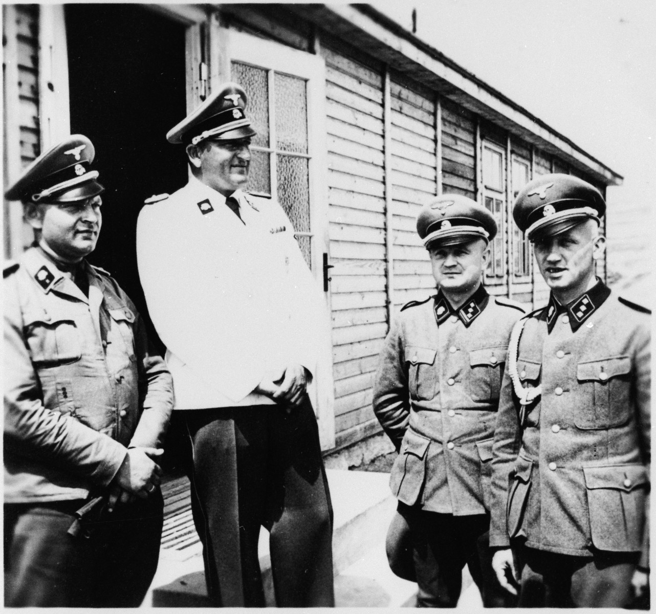 SS-Obersturmbannfuehrer Arthur Roedl (in white), the commandant of Gross-Rosen, in the camp with three members of the SS staff.  His adjutant Kuno Schramm is on the right.