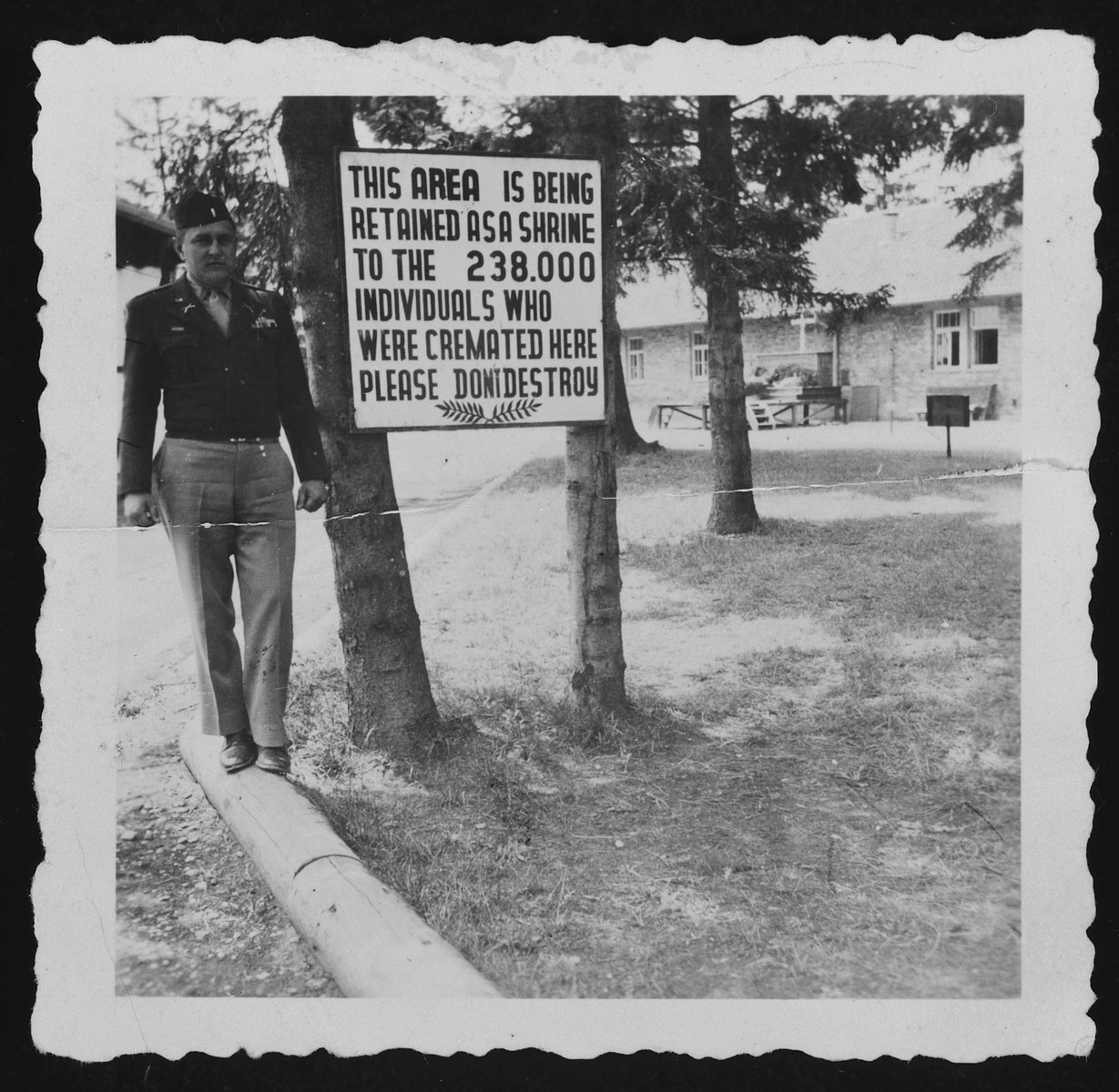 Jospeh H. Williams, deputy-commandant of the Landsberg prison, poses next to a sign marking the site of the crematorium in Dachau that reads, 'This area is being retained a shrine to the 238,000 individuals who were cremated here.  Please do not destroy.'