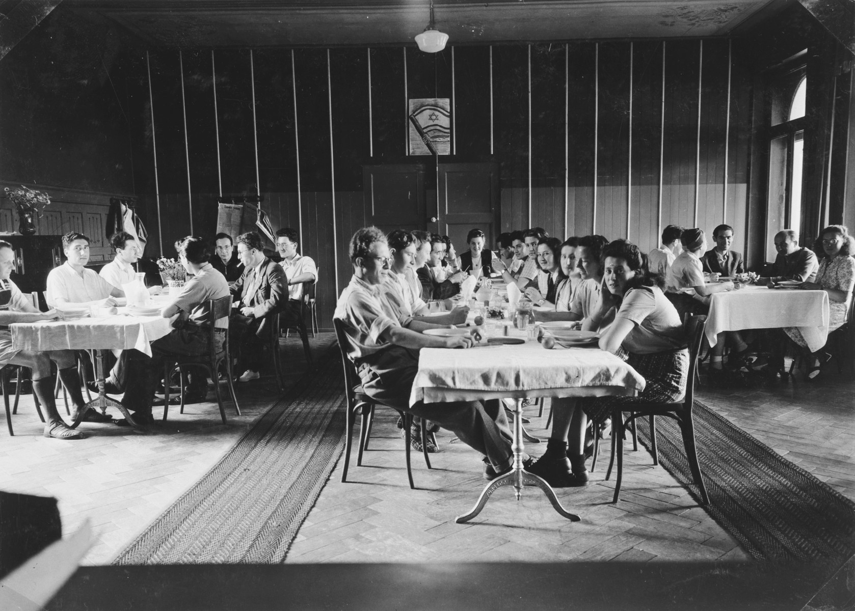 Young Zionists eat in the dining hall of a kibbutz hachshara in Loosdrecht.  Among those pictured is Letty Rudelsheim.
