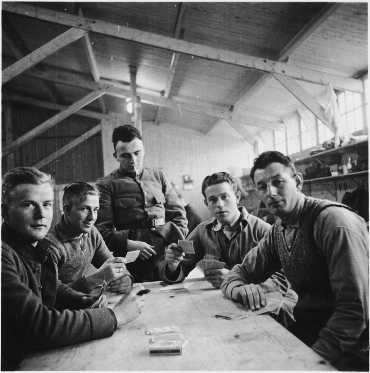 Dutch soldiers play cards inside a barracks during the Phony War.  Standing in the center is David Van Gelder.