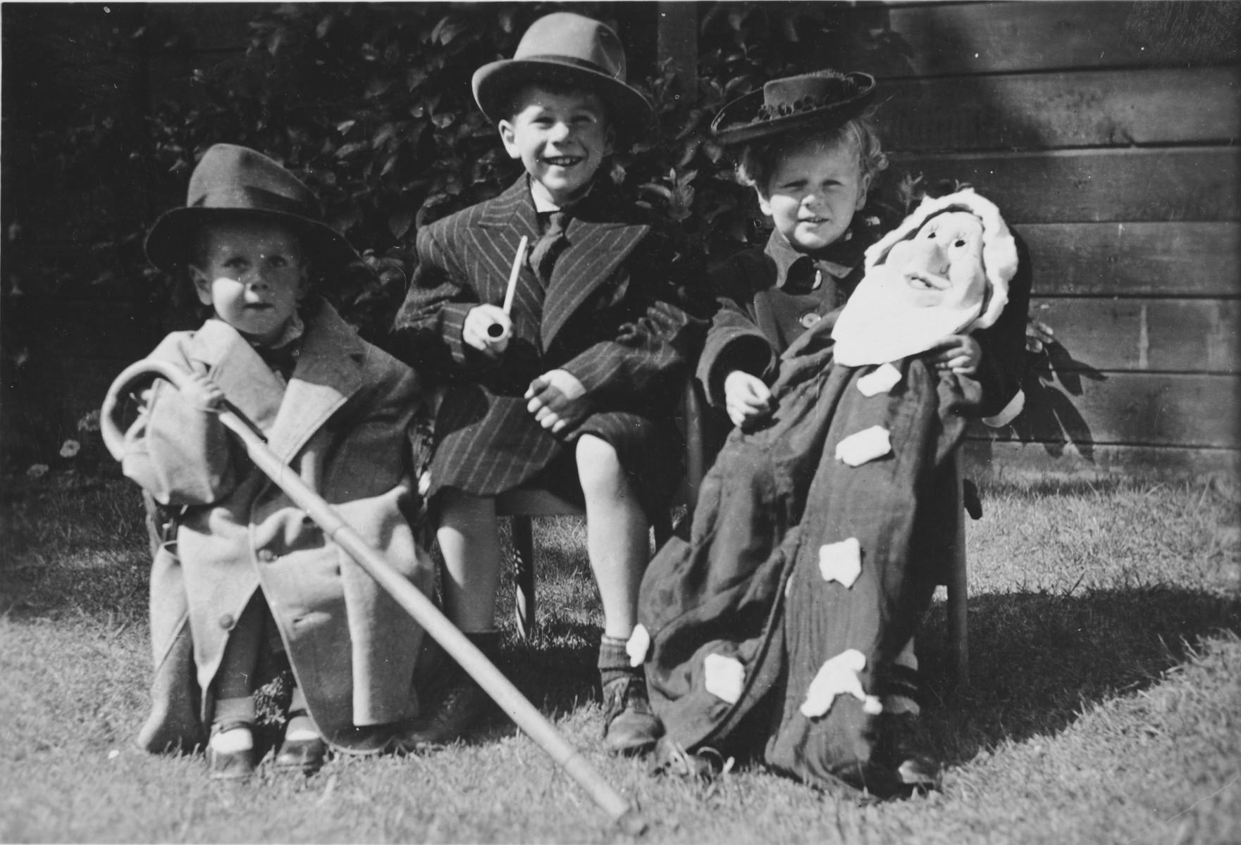 Group portrait of a three Jewish Dutch children wearing costumes.