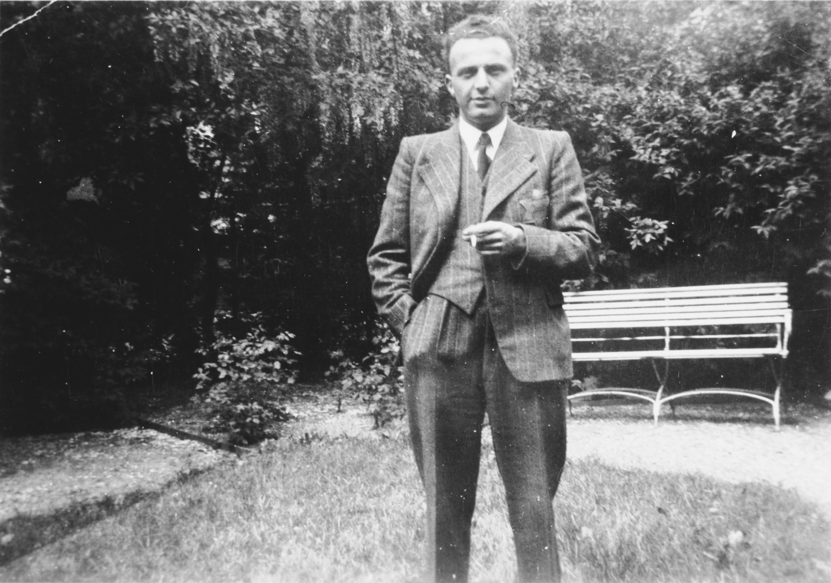 A Jewish Dutch man wearing a Star of David poses outdoors with a cigarette in his hand.  Pictured is David Van Gelder.