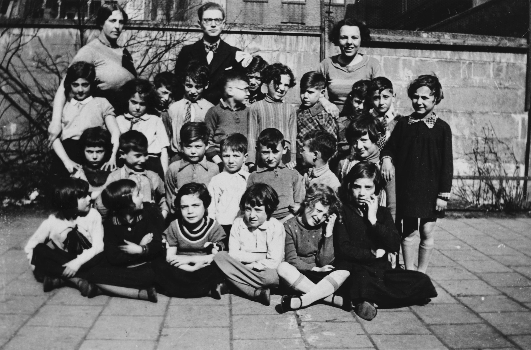 Group portrait of young children and teachers in a class of a Talmud Torah in Amsterdam.  Among those pictured is the teacher, Letty Rudelsheim (back row, right).