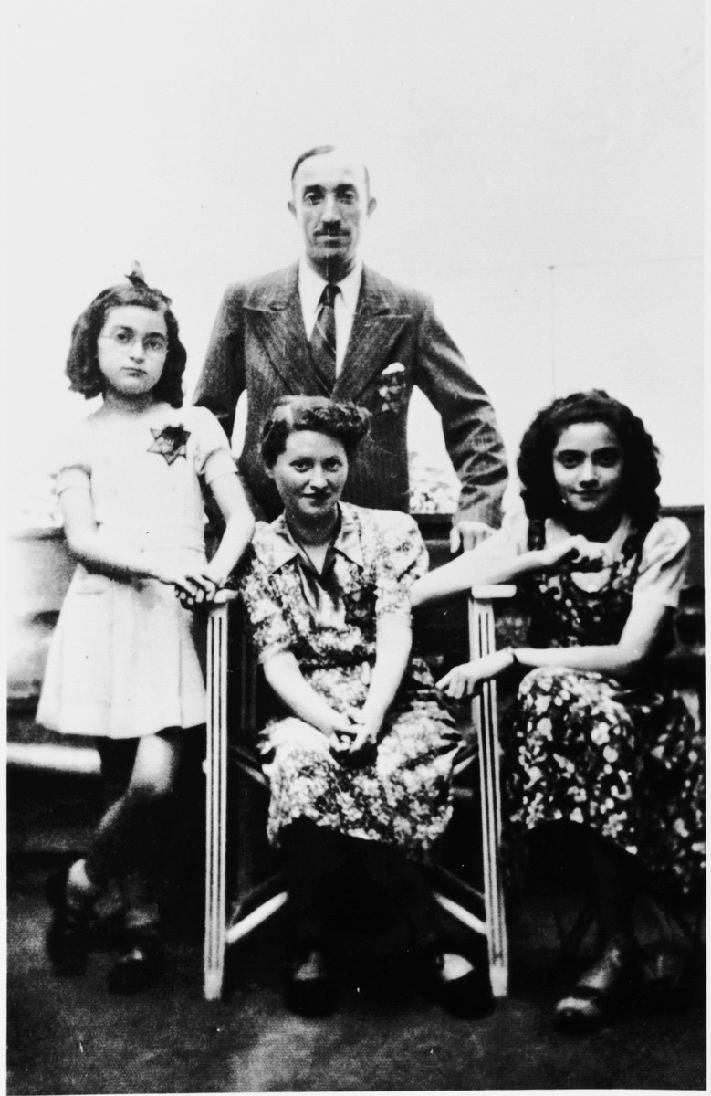 Portrait of a French-Jewish family wearing Jewish stars.  Pictured are Paulette, Samuel, Fanny and Ruth Apfel.