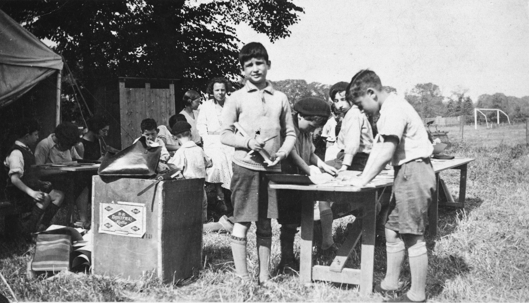 Children work on an outdoor art project in a Jewish summer camp in The Netherlands.  Pictured in the back is the counselor, Letty Rudelsheim.