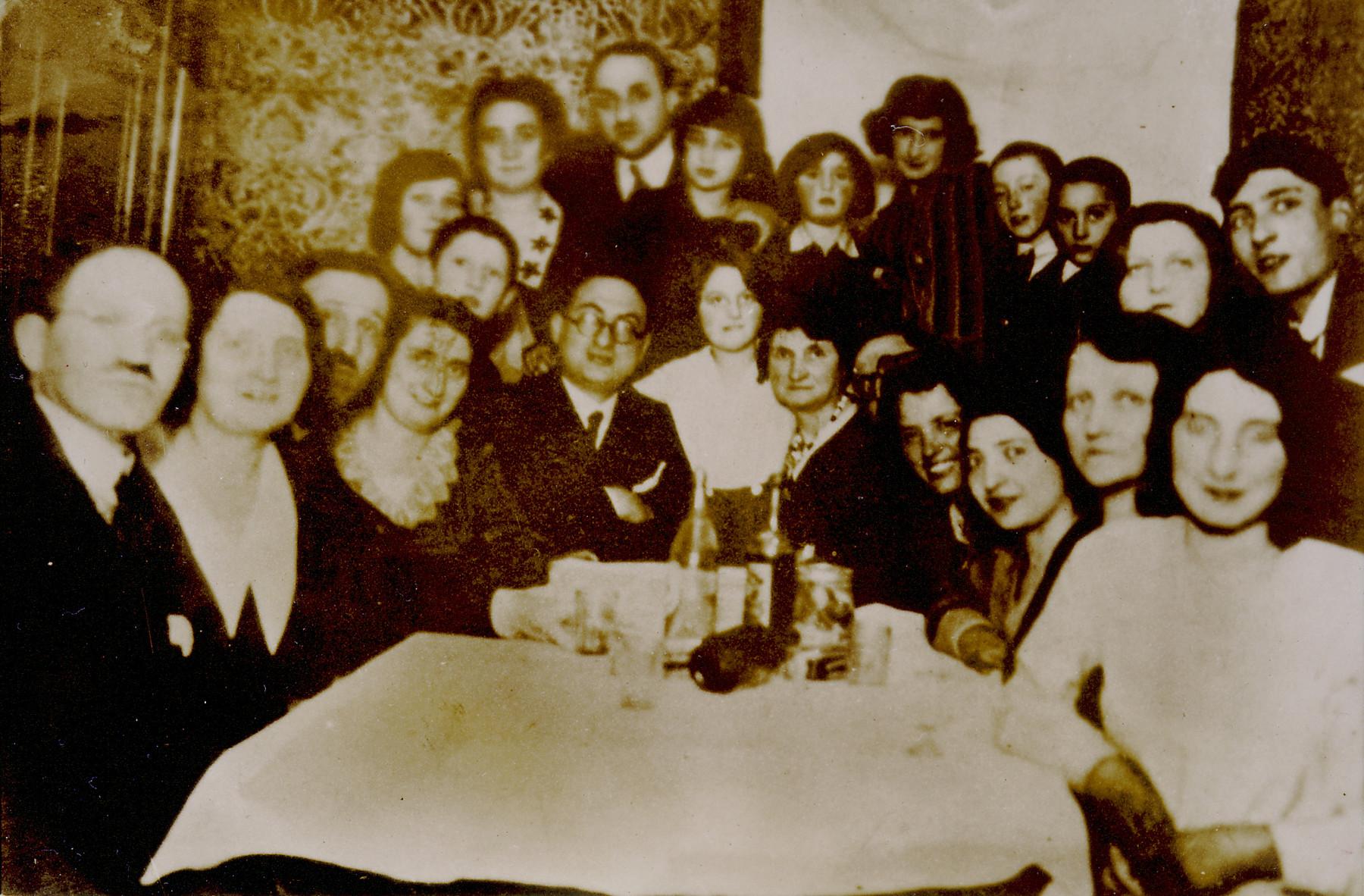 Family of Irving Czestochowski, cousin of Mery Nowogrodski, seated around a table.  Seated from left to right are Mr. Jakubowski, Mrs. Jakubowski, Jankel Lis, Dorcia Lis, Michael Czestochowski, Halinka Lis and Ruchl Czestochowski.  Among those standing are Rywka Czestochowski, Chil Czestochowski, Helcia Chestochowski, Jakubowski and Jakubowski.