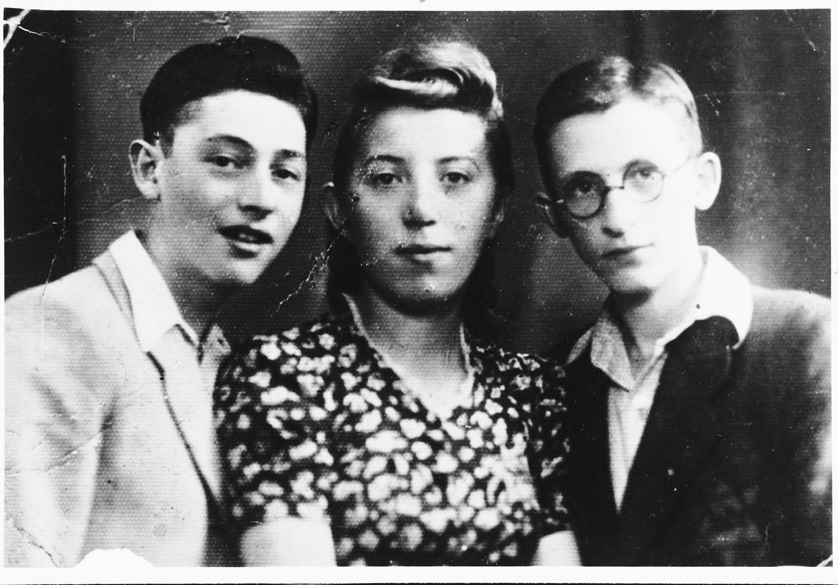 Portrait of three young people in the Bedzin ghetto, one of whom is wearing a Jewish star.  Pictured from left to right are Natan Gipsman, Regina Fajerman and Efroim Poremba.  Regina Fajerman was married to Mendel Magier-they had a child and Regina and the baby were killed at Auschwitz August 1943.