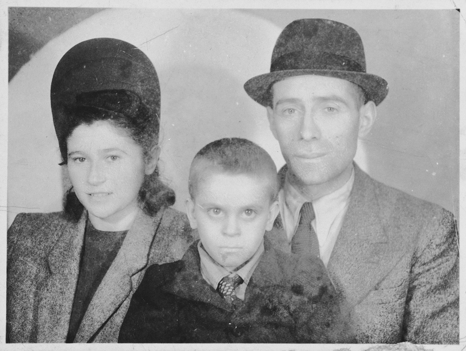 Rabbi and Mrs. Simcha Rotenfeld pose with an adopted orphan who had survived the war in hiding while en route to England.  Pictured from left to right are Sonya Rotenfeld, Elek Rebensztok and Rabbi Simcha Rotenfeld.