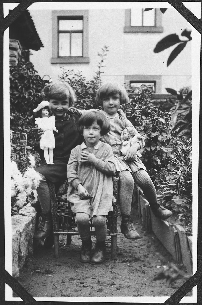 Three young girls holding their dolls pose in a yard.  Pictured are Franzi, Margot Baehr and Inge [probably relatives from Rimpar].