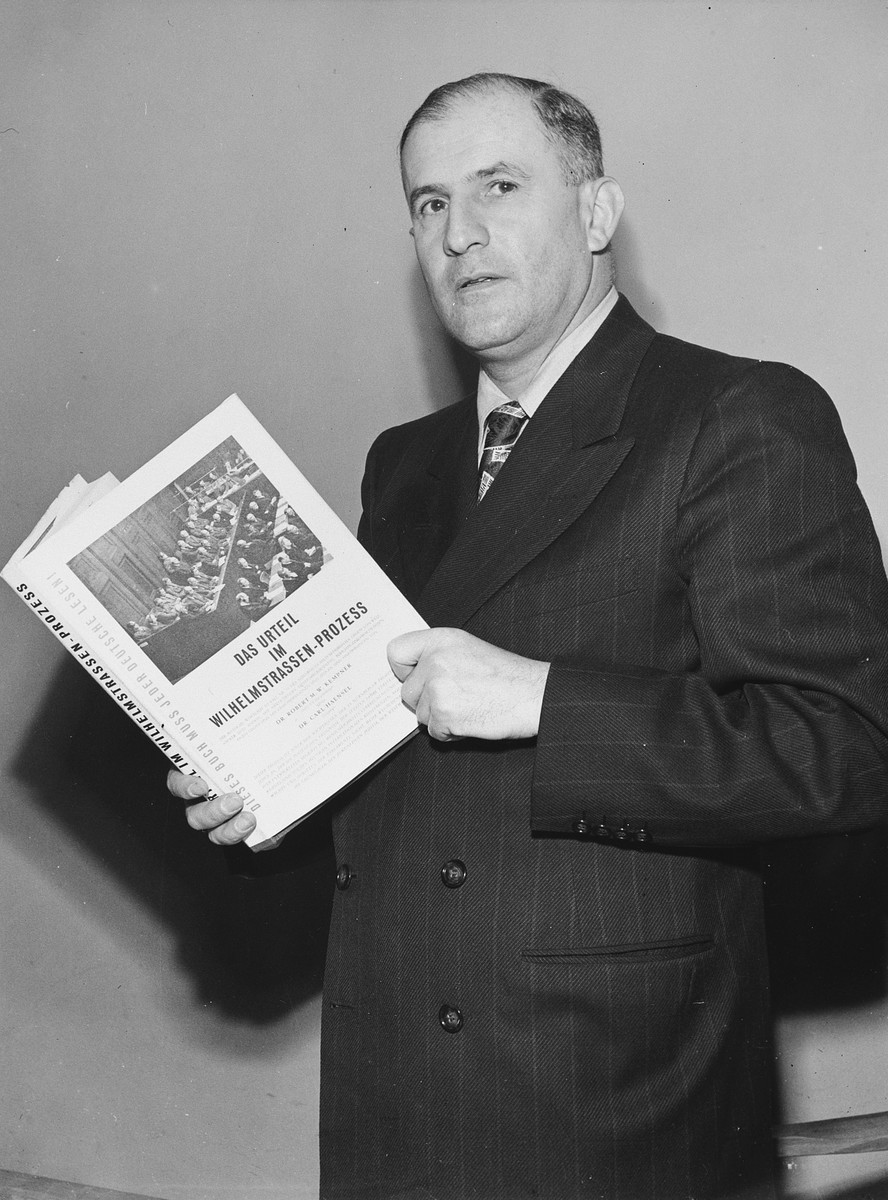 Studio portrait of German-born American attorney, Robert Kempner, holding a book about the Ministries war crime trial which he prosecuted.